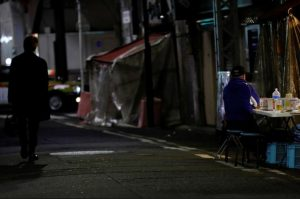 A man drinks at the table outside a bar which opens after 8 PM, the time the government asks restaurants and bars to close by, amid the coronavirus state of emergency in Tokyo, Japan.