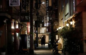A man walks past restaurants which closed after 8 PM, the time the government asks them to close by, amid the coronavirus emergency decree in Tokyo, Japan.